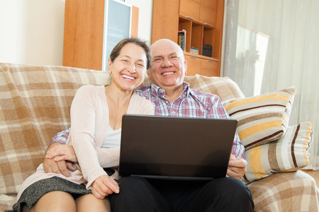 elderly gray-haired man and mature woman  at  laptop on  sofa  photo