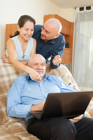Manager helping to couple with laptop photo