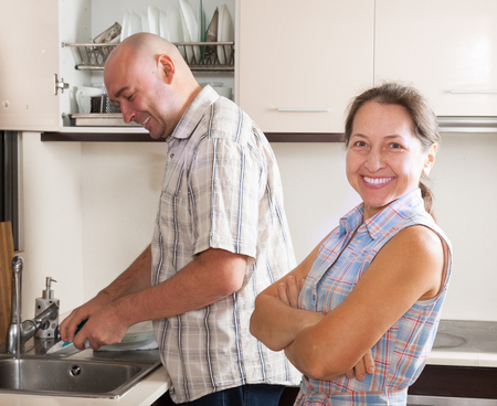 Positive man washing plates and woman in domestic kitchen photo