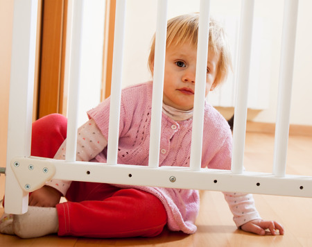 Small baby sitting safety gate of  stairs Stock Photo