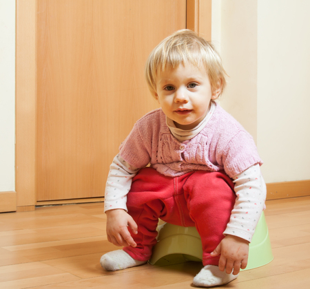 Toddler sitting on potty in home interior