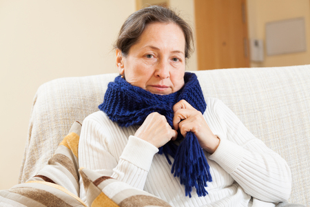 unwholesome: unwell woman in scarf sitting at home