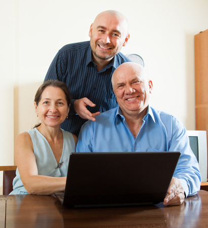 Smiling advisor  standing near mature couple with laptop photo