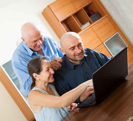 Adult man halping   senior couple with laptop photo