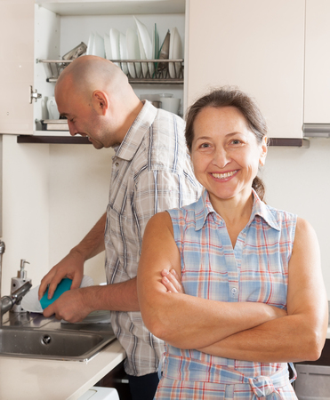 Happy woman and man washing plates in home kitchen photo