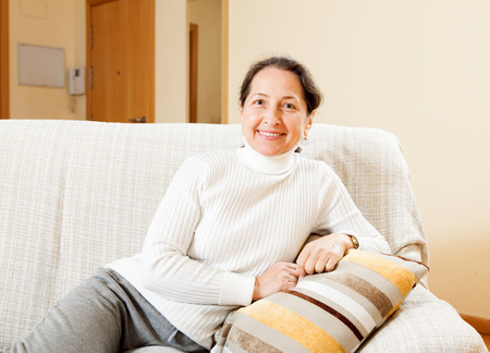 senior woman relaxing on sofa at home photo