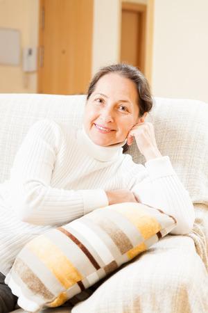 senior woman in white sitting on  sofa   photo