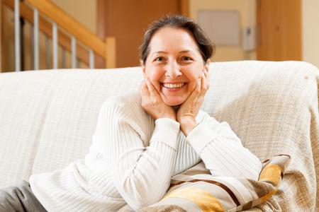senior woman sitting on sofa at home photo