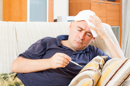 stupes: Illness  man with thermometer stupes  towel to her head at home Stock Photo
