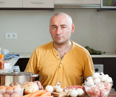 Man in the kitchen who prepare soup photo