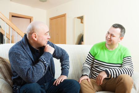 adult men discussing something at home Stock Photo