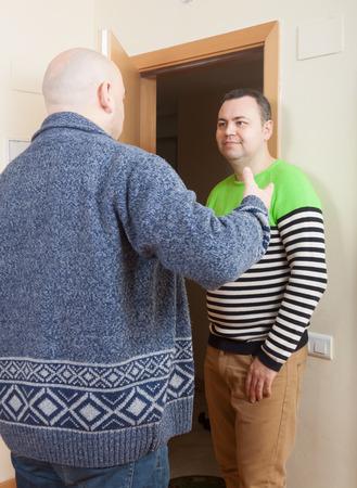 Adult man opening  door his neighbor