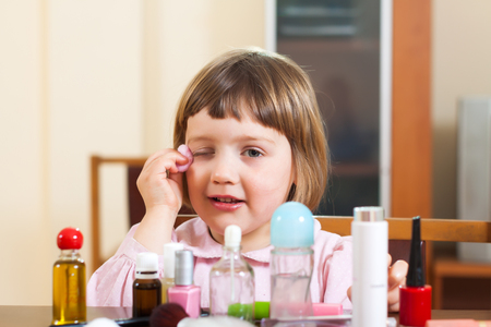 making dresses: little girl at  table with cosmetic products Stock Photo