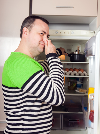 Handsome guy near opened refrigerator in kitchen at home Stock Photo
