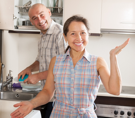 housewife at kitchen and her husband washing plates  photo