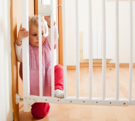 Small baby approaching opening gate of  stairs Stock Photo