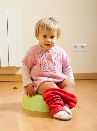 Girl sitting on potty in home interior Stock Photo