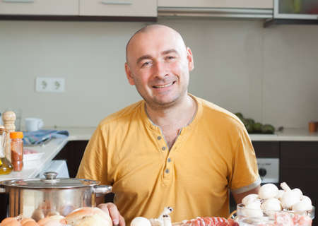 Cheerful man in orange t-shirt in the kitchen photo