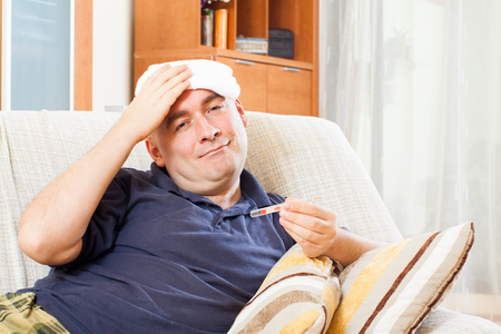 stupes: Illness  man with thermometer stupes  towel to  head at home
