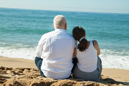 senior man and mature woman together against sea in summer photo