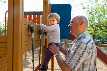 Dad helping his little daughter to climb  ladder on  playground.
