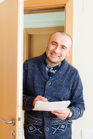 census: Happy man with papers near opens  door Stock Photo