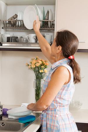 Mature woman washing kitchenware in the kitchen photo