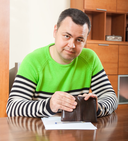 serious man counting his money at  table at home