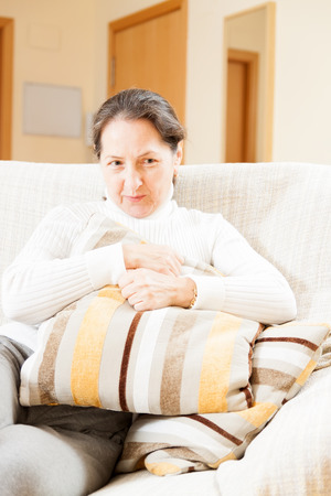 resentful: resentful mature woman in white sitting on  sofa