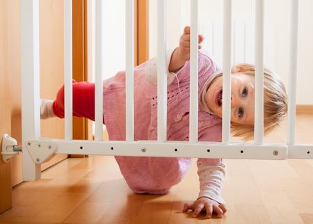 乳幼児: 階段の安全ゲートに近づいて小さな赤ちゃん 写真素材