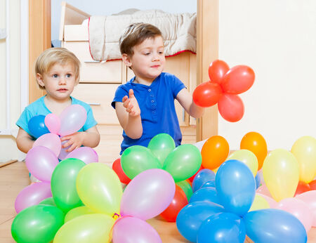Children sitting on  floor with balloons . photo