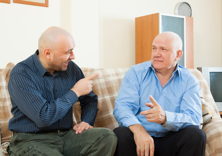 mature men: Mature men talking on the couch at home Stock Photo