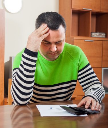 parsimony: frustrated man at  table with  wallet and documents