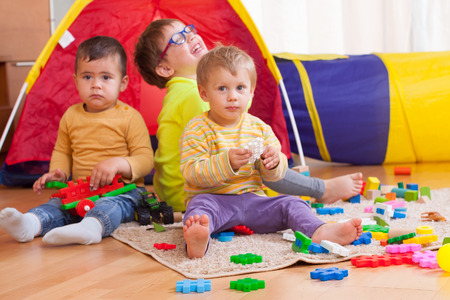 Funny kids playing on  floor with toys. photo