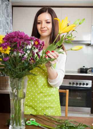 Young woman puting colorful flowers in vase photo