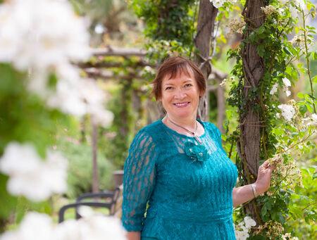 señora mayor: Mujer mayor que recorre en el parque con flores rosas Foto de archivo
