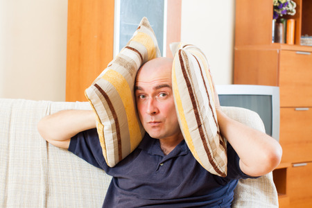 sheltered: Angry man sitting on the couch pillows sheltered Stock Photo