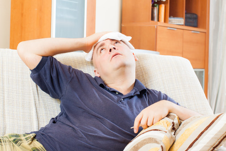 stupes: Sad adult  man having headache holding towel on his head at home Stock Photo