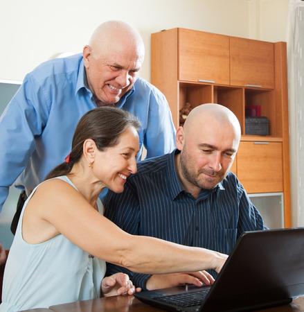 Smiling advisor   near mature couple with laptop photo