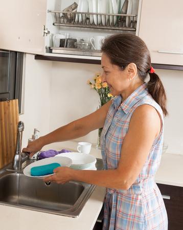 Happy housewife  washing kitchenware in home kitchen photo