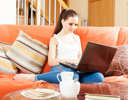 woman sitting on sofa in livingroom with netbook photo