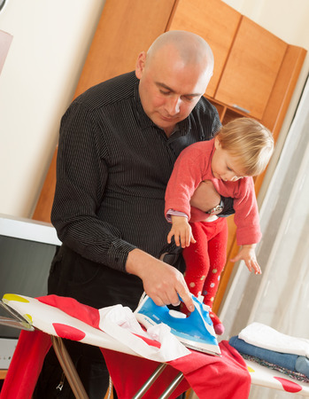 stay home work: dad with baby in  arms for ironing