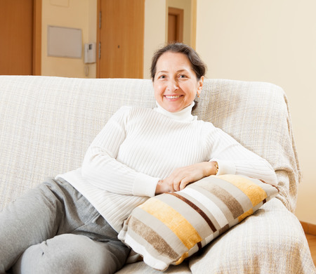 mature woman in white sitting on  sofa photo