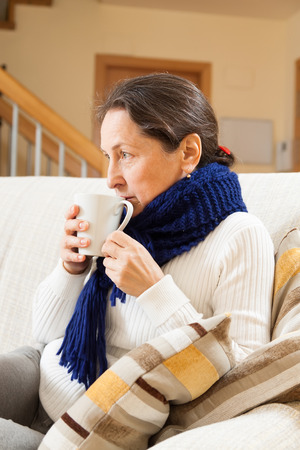 unwholesome: illness woman in warm scarf with hot cup