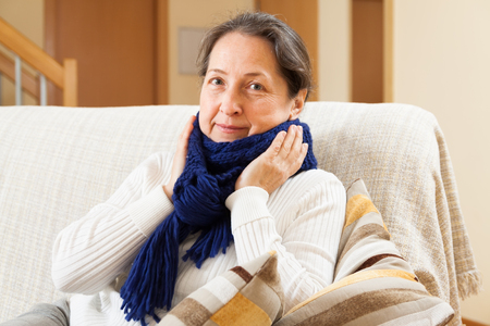 unwholesome: Ailing middle-aged woman sitting on  couch Stock Photo