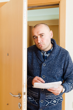 businessman trying to collect money  at home door.