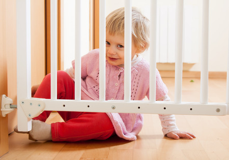 Small baby sitting near safety gate of  stairs Stock Photo