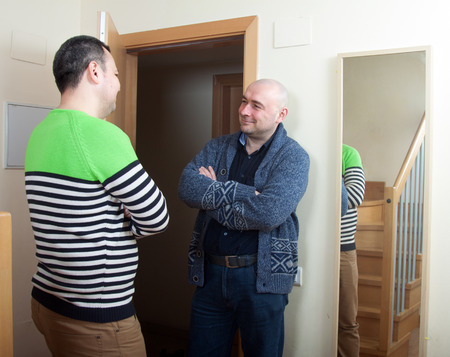 Adult man meeting another man at  door