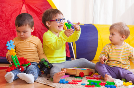 Two girls and boy with toys on  floor at home Stock Photo - 33574241