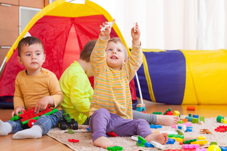 three children playing on  floor with colored toys. photo